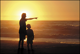 A father watches the ocean with his son