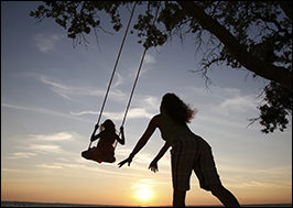A mother pushes her daughter on a tree swing